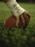 Close-up of the Hand of an American Football Player Holding a Football Lámina fotográfica