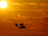 A Pilot Flies a Small Plane Past the Setting Sun Over Lake Winnipesaukee Photographic Print