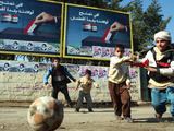 "Iraqi Boys Play Soccer Below the Poster Reading ""To Grant Iraqi Children Better Iraq"" Photographic Print"