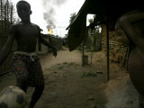 Two Local Children Play Soccer Near Their House While a Gas Flare Burns Photographic Print