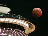 The Full Moon Turns Red and Orange as It Passes the Space Needle Photographic Print