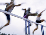 Low Angle View of Three Men Jumping over a Hurdle Photographic Print