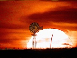 A Blazing Sun Drops Behind a Windmill Photographic Print