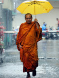 A Buddhist Monk Walks in the Rain on a Street in Bangkok Photographic Print