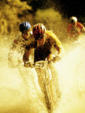 Young Men Riding Bicycles Through Water Photographic Print