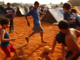 Children Play Soccer Between Tents Placed on a Dusty Lot Photographic Print