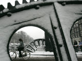 A Cyclist Passes a Draw Bridge as Snow Covers the City Center of Amsterdam Photographic Print