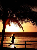 A Afternoon Runner Passes Under a Palm Tree as the Sun Sets Behind Impressão fotográfica