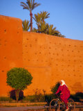 Veiled Woman Bicycling Below Red City Walls, Marrakech, Morocco Photographic Print by John & Lisa Merrill