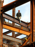 A Construction Worker Stands on a Steel Beam While Working on a High Rise Building Photographic Print