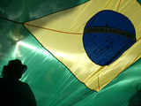 A Vendor Walks Behind a Big Brazilian Flag Photographic Print