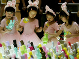 A Group of Girls Dressing as Bunny Rabbits Play with Rabbit Figures Photographic Print