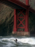A Surfer is Dwarfed by the Northern End of the Golden Gate Bridge While Riding the Waves Photographic Print