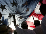 Immigration Rights Demonstrators Hold a U.S. Flag Aloft During a March Along Wilshire Boulevard Lámina fotográfica