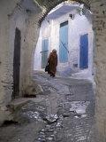 Traditionally Dressed Woman along Cobblestone Alley, Morocco Fotodruck von John & Lisa Merrill