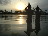 Hindu Devotees Offer Prayers to the Sun God at Sunset Photographic Print