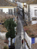 Woman in Narrow Alley with Whitewashed Houses, Obidos, Portugal Photographic Print by John & Lisa Merrill