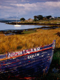 Rowboat Hauled up on Shore of Inlet with Moored Yacht, Ireland Photographic Print by Richard Cummins