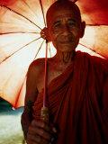 Smiling Monk Holding Umbrella, Mrauk U, Myanmar (Burma) Fotodruck von Frank Carter