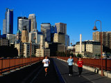 Women Jogging Across Stone Arch Bridge with City Skyline Beyond, Minneapolis, USA Photographic Print by Richard Cummins