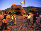 People Playing Volleyball Outside Indaba Bar, Cape Maclear, Malawi Photographie par Johnson Dennis