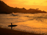 Surfer Standing at Waimea Bay at Sunset, Waimea, U.S.A. Photographic Print by Ann Cecil