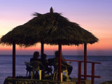 Cliffside Table at Pickled Parrot at Sunset, Negril, Jamaica Photographic Print by Holger Leue