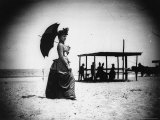Georgiana Parker, in a Dress and Hat, Carrying a Parasol with a Group People at the beach Premium Photographic Print by Wallace G. Levison