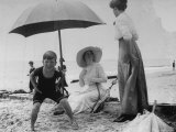 Mildred Lord Talking to Mrs. Simpson as Her Son Chester Lord Peers Into Camera at Sea Gate Beach Premium Photographic Print by Wallace G. Levison