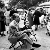 Vincente Minnelli with coffee sitting in chair with Daughter Liza at Outdoor Children's Party Being Premium Photographic Print by J. R. Eyerman