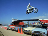 Daredevil Motorcyclist Evil Knievel in Mid Jump over a Row of Cars Premium Photographic Print by Ralph Crane