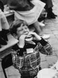 Hollywood Child Timmy Garry at Children's party Dressed in Cowboy Outfit eating a Hamburger Lámina fotográfica por J. R. Eyerman