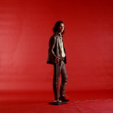 Rock Star Jim Morrison of the Doors Standing Alone Next to Microphone in Front of a Red Backdrop Premium Photographic Print by Yale Joel