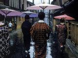 Geishas Carry Umbrellas of Oiled Japanese Paper Wearing Geta Walking in Rain, Gion Geisha Quarter Premium Photographic Print by Eliot Elisofon