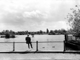 British Actor Alec Guinness Sitting Alone by Lake in a Park Lámina fotográfica de primera calidad por Cornell Capa
