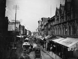 Bustling View of Fulton St, with Rows of Shops and Horse Drawn Carriages Photographic Print by Wallace G. Levison