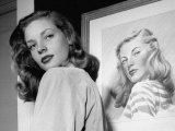 Actress Lauren Bacall Posing in Front of Portrait Drawing of Herself in Suite at the Gotham Hotel Premium Photographic Print by Nina Leen