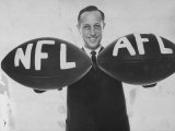 National Football League Commissioner Pete Rozelle Holding Together 2 Footballs Labeled NFL and Afl Premium Photographic Print by Bob Gomel