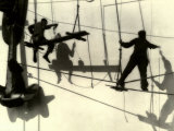 Silhouettes of Workers Using Rope Rigging to Clean and Paint the Side of a Ship Premium Photographic Print by J. Kauffmann