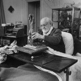 Henri Matisse Sculpting Nude Female Figure While Sitting in Bed in His Apartment Premium Photographic Print by Dmitri Kessel