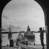 US Soldier Standing Guard over Section of Panama Canal, Battleship with Full Crew on Deck Photographic Print by Thomas D. Mcavoy