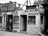Shack Like Black Jeweler Shop Next to Food Store Covered with Ads in a Slum Section of the City. Photographic Print by Alfred Eisenstaedt