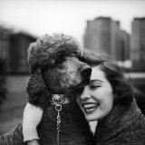 Woman Profiling a Big Smile While Adoring Her Poodle Wearing Large Swiss Watch on Dog Collar Photographic Print by Yale Joel