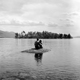 Young Couple Embracing on Small Rock Protruding from the Waters of Lake George Reproduction photographique par Nina Leen