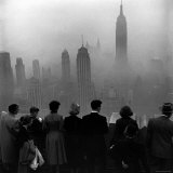 People on Top of a Building Looking Down Into Downtown Misty Smog covering Empire state Building Fotografie-Druck von Eliot Elisofon