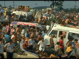 Crowd of people, some Sitting on Top of Cars and Busses, During the Woodstock Music/Art Fair Photographic Print by John Dominis