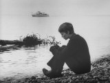 Actress Mia Farrow Pensively Sitting on Rocky Shore of Lake Geneva as Passenger Boat Passes By Premium Photographic Print by Bill Eppridge