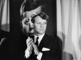 Robert F. Kennedy Campaigning in Front of Poster Portrait of His Brother President John F. Kennedy Premium Photographic Print by Bill Eppridge