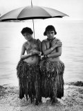 Young Yap Island ladies sporting traditional Grass Skirts, Sharing umbrella in the Caroline Islands Photographic Print by Eliot Elisofon