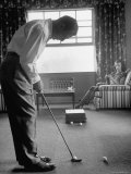 Golfer Ben Hogan Practicing Putting in His town house with Wife Valerie Watching from Armchair Lámina fotográfica de primera calidad por Loomis Dean